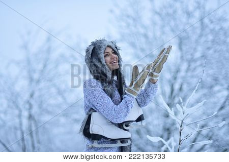 Sport, activity, health. Happy woman smile with figure skates at trees in snow. Vacation, holidays, hobby, lifestyle. Ice skating concept. Girl with skating shoes in winter clothes in snowy forest.