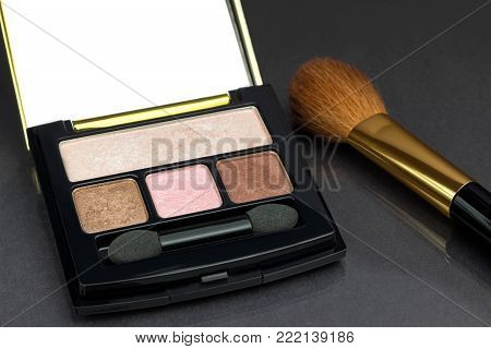 Eyeshadow palette of brown, beige and pink colors with case on black background.