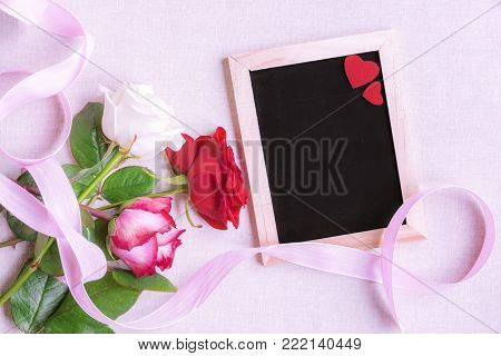 Roses and chalkboard with red hearts - Lovely bouquet of multicolored roses, tied with a pink ribbon, near a blank chalkboard decorated with two red hearts, on a pink background.