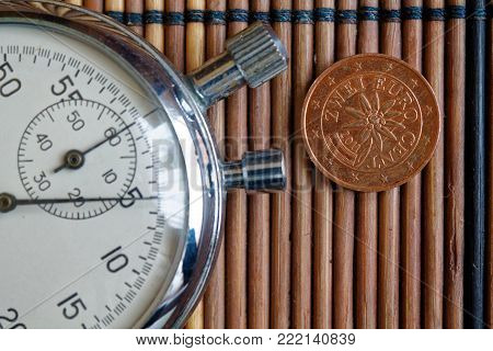 Euro coin with a denomination of two euro cents and stopwatch on wooden table - back side