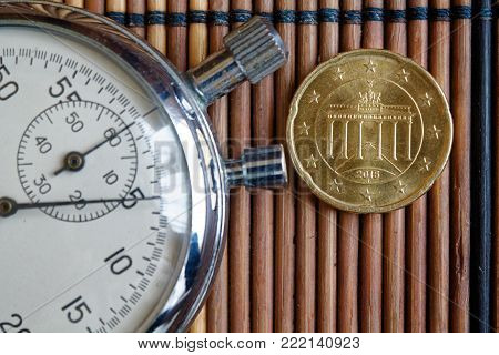 Euro coin with a denomination of 20 euro cents and stopwatch on wooden table - back side