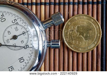 Euro coin with a denomination of 50 euro cents and stopwatch on wooden table - back side