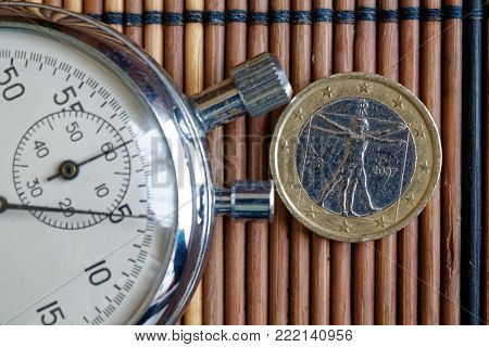 Euro coin with a denomination of 1 euro and stopwatch on wooden table - back side