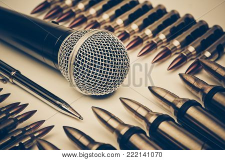 Microphone vs. Bullets / Freedom of the press is at risk concept / World press freedom day concept