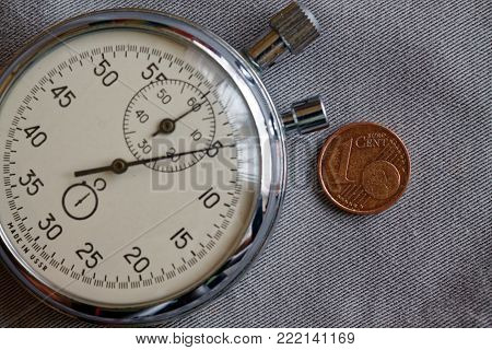 Euro coin with a denomination of 1 euro cent and stopwatch on gray denim backdrop - business background