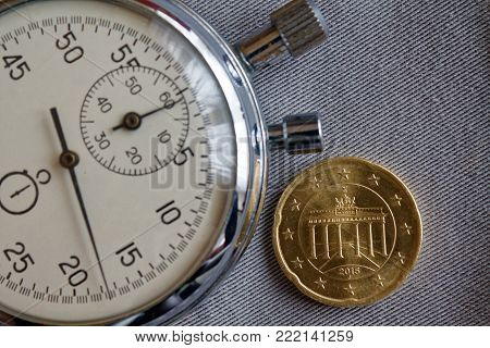 Euro Coin With A Denomination Of 20 Euro Cents (back Side) And Stopwatch On Gray Denim Backdrop - Bu