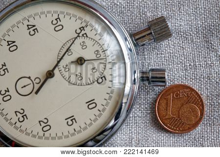 Euro coin with a denomination of 1 euro cent and stopwatch on white flax backdrop - business background