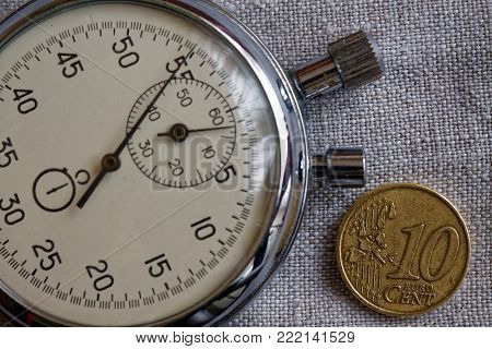 Euro coin with a denomination of ten euro cents (back side) and stopwatch on white linen canvas backdrop - business background