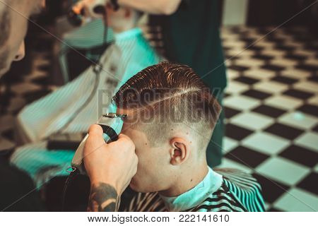 Haircut men Barbershop. Men's Hairdressers barbers. Barber cuts the client machine for haircuts.