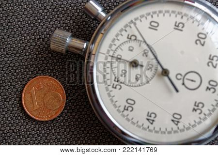 Euro Coin With A Denomination Of One Euro Cent And Stopwatch On Brown Denim Backdrop - Business Back