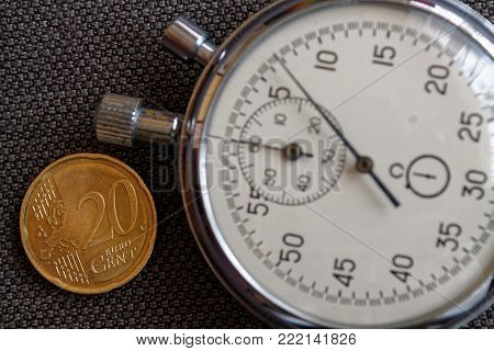 Euro Coin With A Denomination Of Twenty Euro Cents And Stopwatch On Brown Denim Backdrop - Business