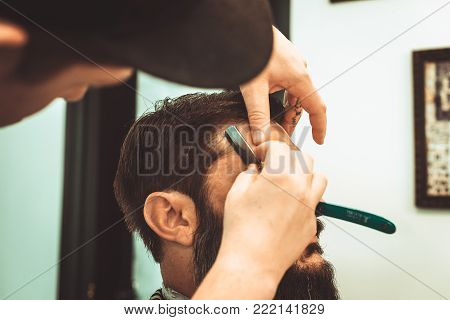 Haircut men BarberShop. Mens Hairdressers barbers. Barber cuts the client razor for haircuts.