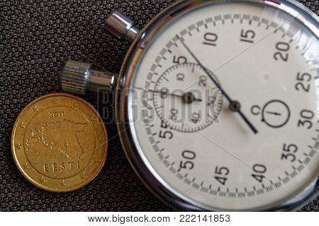 Euro Coin With A Denomination Of 50 Euro Cents (back Side) And Stopwatch On Brown Denim Backdrop - B