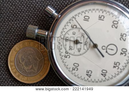 Turkish Coin With A Denomination Of 1 Lira (back Side) And Stopwatch On Brown Denim Backdrop - Busin