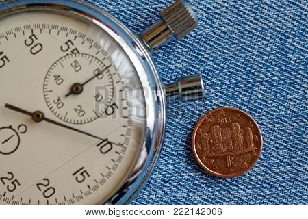Euro Coin With A Denomination Of One Euro Cent (back Side) And Stopwatch On Blue Denim Backdrop - Bu