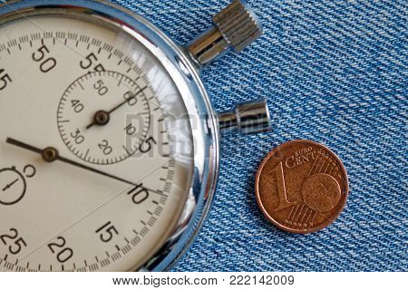 Euro Coin With A Denomination Of 1 Euro Cent And Stopwatch On Blue Denim Backdrop - Business Backgro