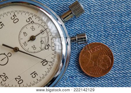 Euro Coin With A Denomination Of Two Euro Cents And Stopwatch On Blue Denim Backdrop - Business Back