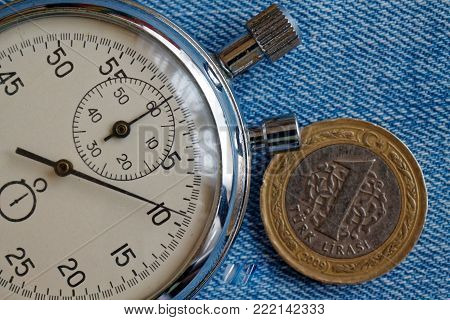 Turkish coin with a denomination of one lira and stopwatch on old blue jeans backdrop - business background