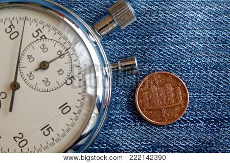 Euro coin with a denomination of 1 euro cent (back side) and stopwatch on worn jeans backdrop - business background