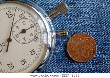 Euro Coin With A Denomination Of Two Euro Cents And Stopwatch On Worn Blue Jeans Backdrop - Business