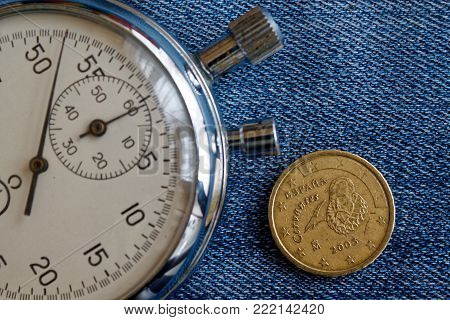 Euro Coin With A Denomination Of 10 Euro Cents (back Side) And Stopwatch On Worn Jeans Backdrop - Bu