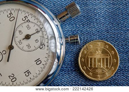 Euro Coin With A Denomination Of 20 Euro Cents (back Side) And Stopwatch On Worn Jeans Backdrop - Bu