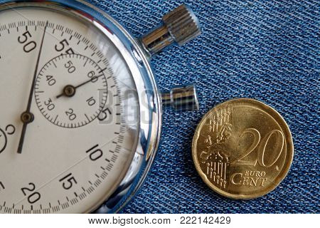 Euro Coin With A Denomination Of Twenty Euro Cents And Stopwatch On Worn Blue Jeans Backdrop - Busin