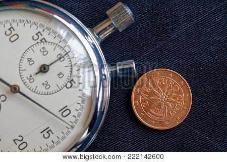 Euro coin with a denomination of 2 euro cents (back side) and stopwatch on worn black jeans backdrop - business background