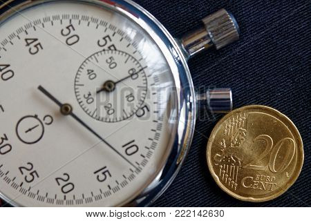 Euro Coin With A Denomination Of Twenty Euro Cents And Stopwatch On Black Jeans Backdrop - Business