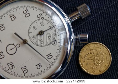 Euro Coin With A Denomination Of 10 Euro Cents (back Side) And Stopwatch On Worn Black Jeans Backdro