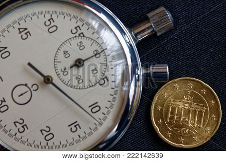 Euro Coin With A Denomination Of 20 Euro Cents (back Side) And Stopwatch On Worn Black Jeans Backdro