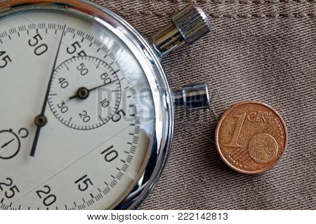 Euro Coin With A Denomination Of One Euro Cent And Stopwatch On Worn Beige Denim Backdrop - Business