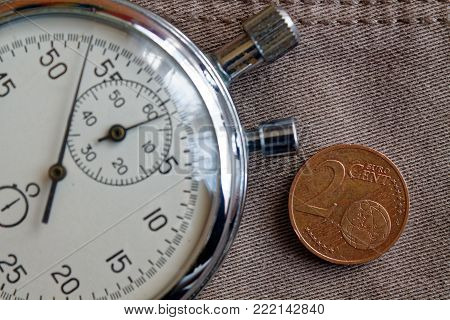 Euro Coin With A Denomination Of Two Euro Cents And Stopwatch On Worn Beige Denim Backdrop - Busines