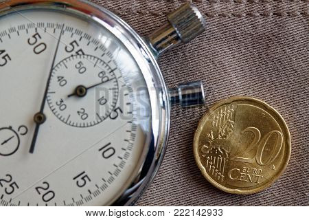 Euro Coin With A Denomination Of Twenty Euro Cents And Stopwatch On Worn Beige Denim Backdrop - Busi