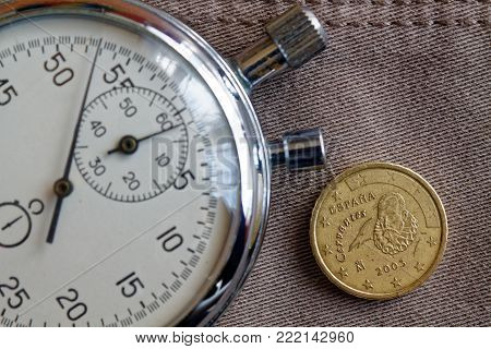 Euro Coin With A Denomination Of 10 Euro Cents (back Side) And Stopwatch On Beige Denim Backdrop - B