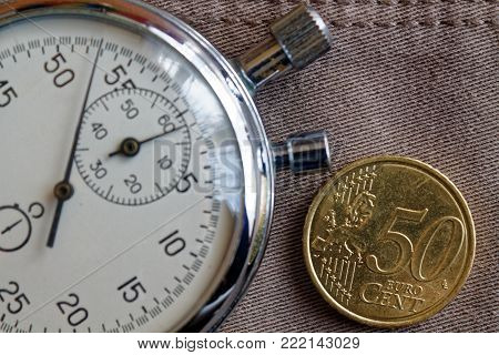 Euro Coin With A Denomination Of Fifity Euro Cents And Stopwatch On Worn Beige Denim Backdrop - Busi