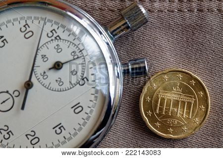 Euro Coin With A Denomination Of 20 Euro Cents (back Side) And Stopwatch On Beige Denim Backdrop - B