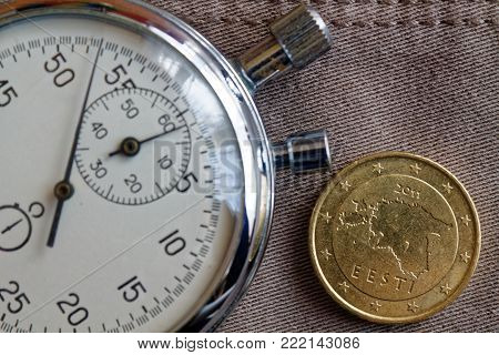 Euro Coin With A Denomination Of 50 Euro Cents (back Side) And Stopwatch On Beige Denim Backdrop - B