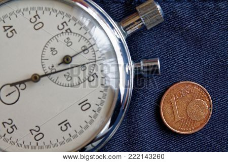 Euro Coin With A Denomination Of One Euro Cent And Stopwatch On Old Blue Jeans Backdrop - Business B
