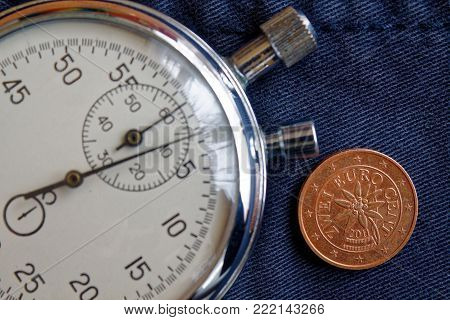 Euro Coin With A Denomination Of 2 Euro Cents (back Side) And Stopwatch On Old Blue Denim Backdrop -