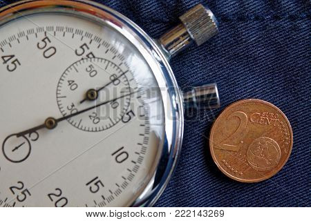 Euro Coin With A Denomination Of Two Euro Cents And Stopwatch On Old Blue Jeans Backdrop - Business