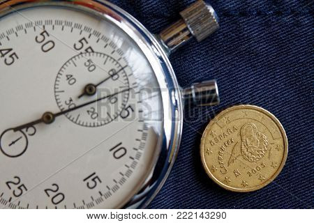 Euro coin with a denomination of 10 euro cents (back side) and stopwatch on old blue denim backdrop - business background