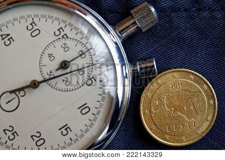 Euro coin with a denomination of 50 euro cents (back side) and stopwatch on old blue denim backdrop - business background