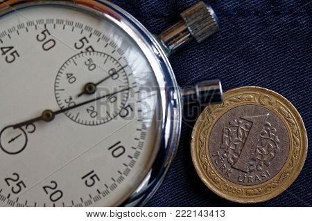 Turkish Coin With A Denomination Of One Lira And Stopwatch On Dark Worn Blue Jeans Backdrop - Busine
