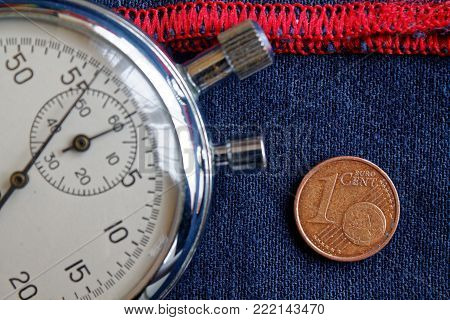 Euro Coin With A Denomination Of One Euro Cent And Stopwatch On Worn Blue Denim With Red Stripe Back