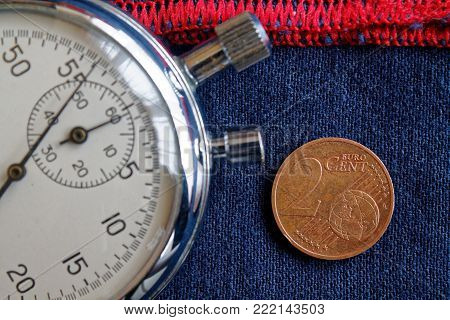 Euro Coin With A Denomination Of Two Euro Cents And Stopwatch On Worn Blue Denim With Red Stripe Bac