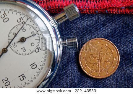 Euro Coin With A Denomination Of 5 Euro Cents (back Side) And Stopwatch On Worn Blue Jeans With Red