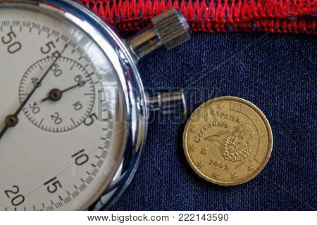 Euro Coin With A Denomination Of 10 Euro Cents (back Side) And Stopwatch On Worn Blue Jeans With Red