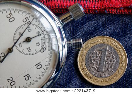Turkish coin with a denomination of one lira and stopwatch on blue denim with red stripe backdrop - business background