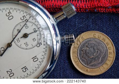 Turkish coin with a denomination of 1 lira (back side) and stopwatch on blue jeans with red stripe backdrop - business background
